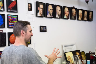 Artist Brent Holland with collection of self-portraits
