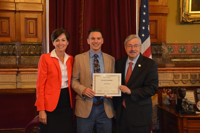Gov. Reynolds and Former Gov. Brandstad presenting Iowa Arts Fellowship to Artist Brent Holland